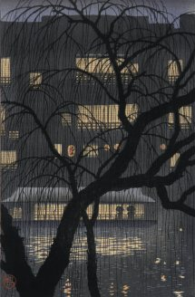 a black silhouette of a tree in front of a large building with windows aglow at night