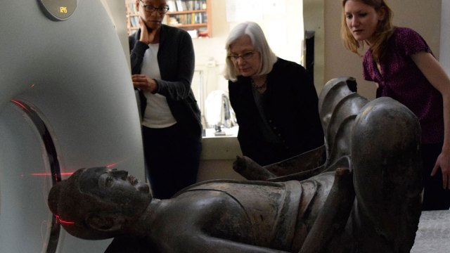 3 conservators look on as the freer buddha enters a ct scanning machine