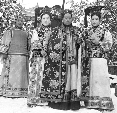 Cixi is flanked by the photographer's sisters, Deling and Rongling. Behind them is their mother, Madame Yugeng