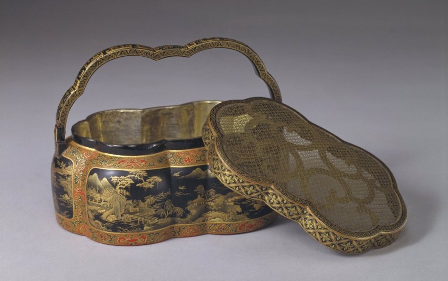 gold and black rounded box with curved handle and grated lid