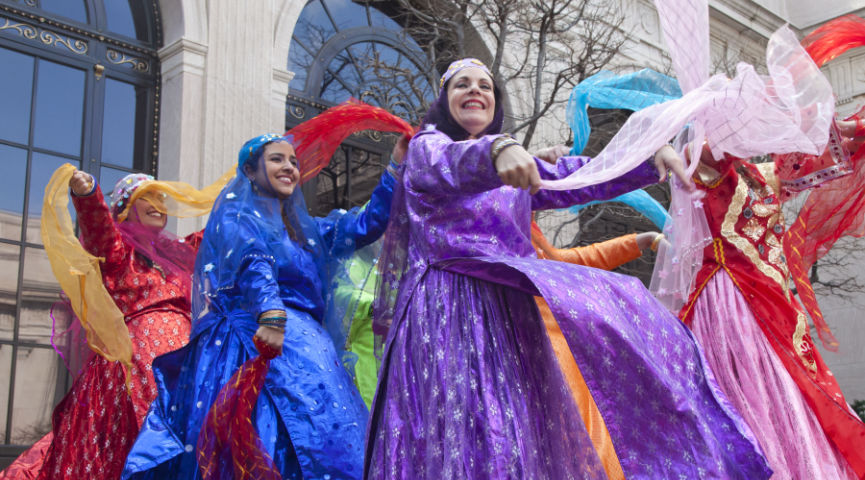 women dancing and twirling scarves in brightly colored dresses