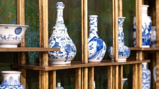 blue and white vases on gilded shelving in the green and blue peacock room