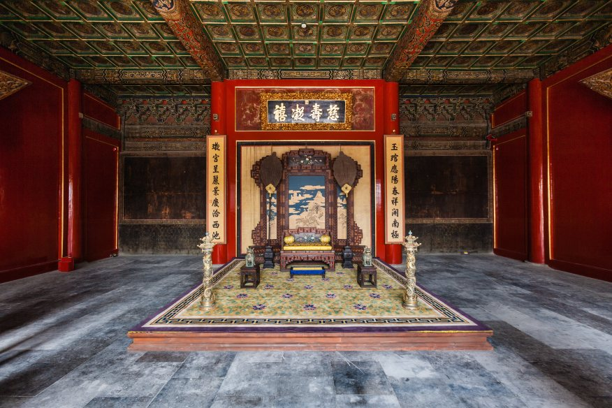 photo of interior of palace room with central throne and highly decorated ceiling and walls