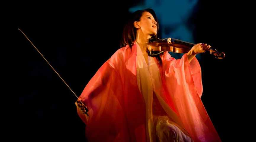 female in pink robe playing violin