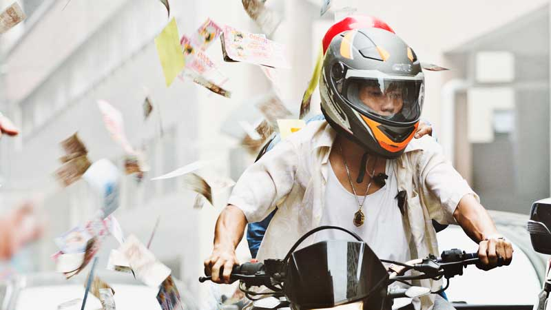 money flying around a motorcycle rider