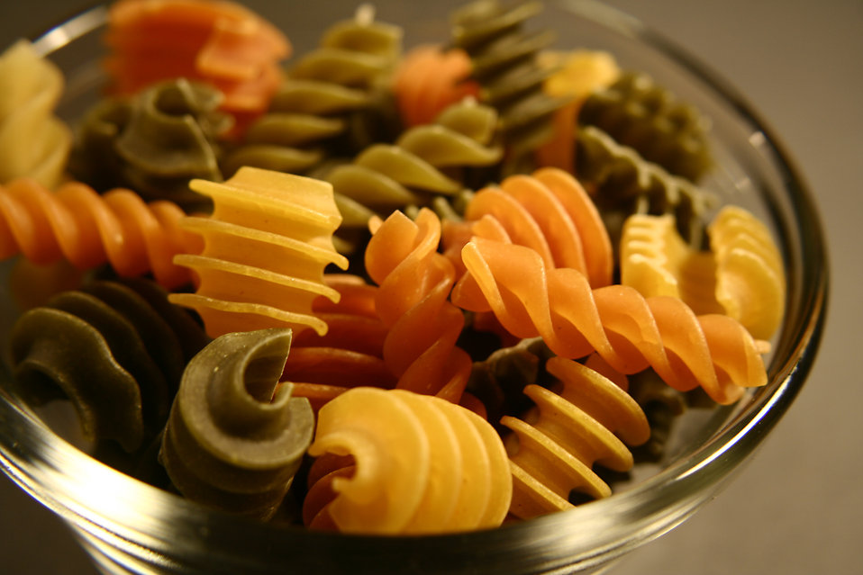 This photograph depicts a small glass bowl filled with uncooked, carbohydrate-rich, multi-colored rotini pasta.