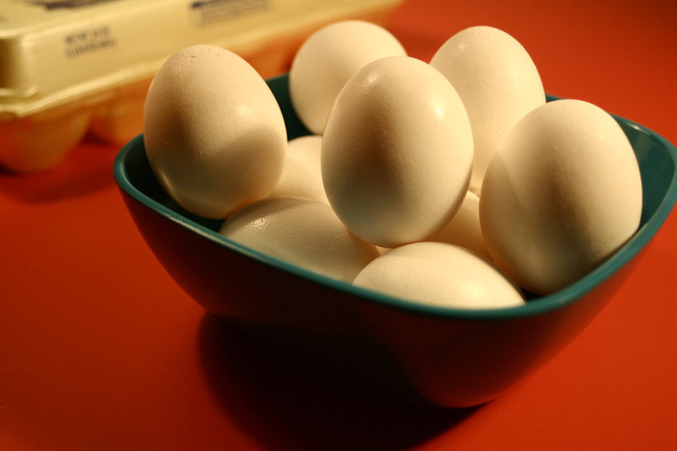 Depicted in this photograph is a green ceramic bowl that had been filled with fresh store-bought, uncooked chicken eggs. The yellow carton from which these eggs were taken can be seen in the background.