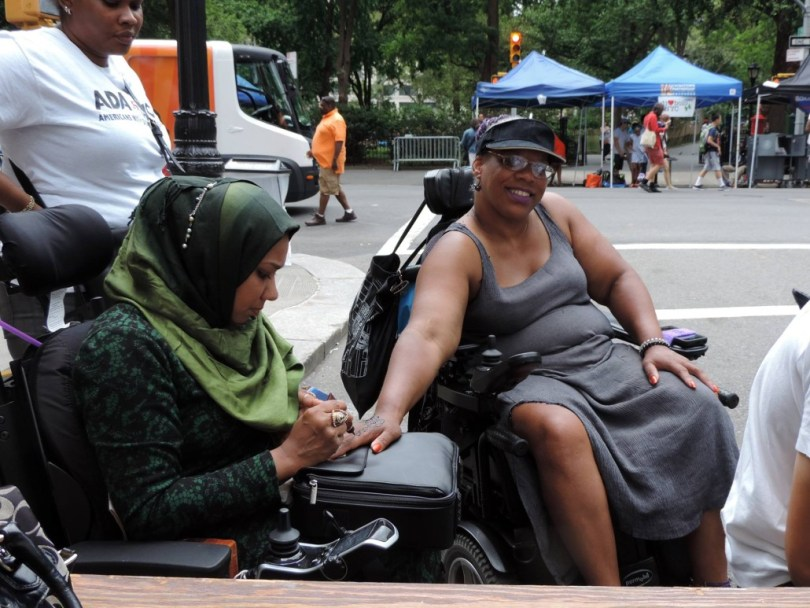 Israt Noor paints a woman's hand at Disability Pride NYC.