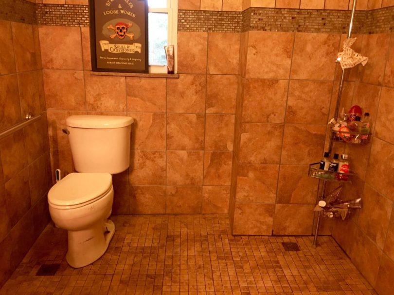 Toilet in a wet bath with a 3 foot wide space beside it to accommodate a wheelchair.