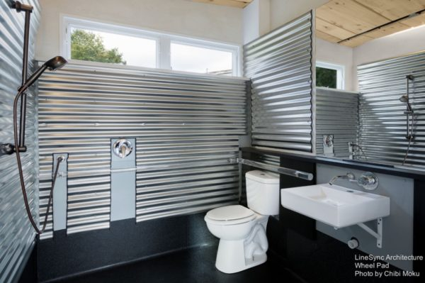 Wheel Pad wheelchair accessible tiny house bathroom with wet bath and corrugated metal walls.