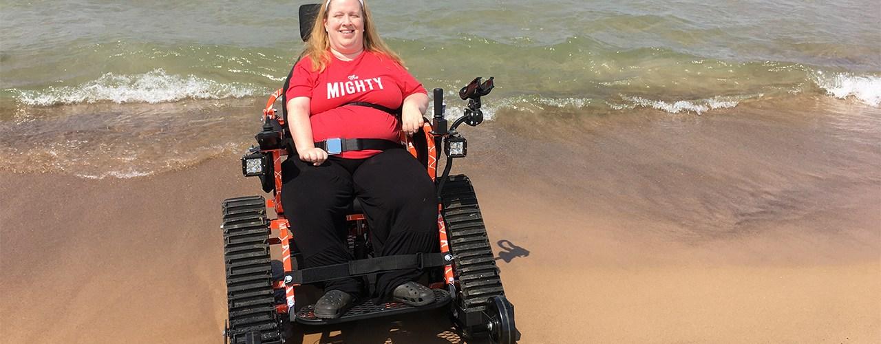 Karin Willison riding in a tank wheelchair on the beach.