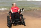 Karin Willison riding in a tank wheelchair on the beach.