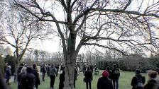Trauernde auf dem Feld für anonyme Urnenbestattung