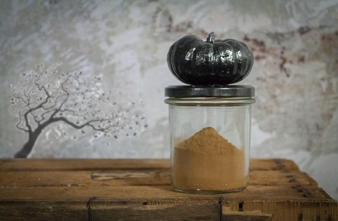 Kürbiskuchen-Gewürz oder Pumpkin pie spice ist in einem Glas. Das Glas hat einen Deckel mit einem Metallkürbis darauf. Das Glas steht auf einer alten Holzkiste, vor einer malerischen Wand. Auf der Wand ist als Graphik ein Baum der herbstlich die Blätter verliert.