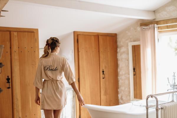Mariée se promène dans la baignoire en robe de soie rose avec le mot