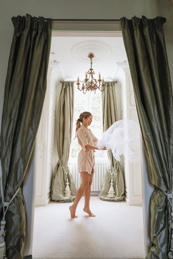 La mariée est debout dans l'embrasure de la porte encadrée par des rideaux de soie verte et joue avec le bas de son voile accroché à la porte