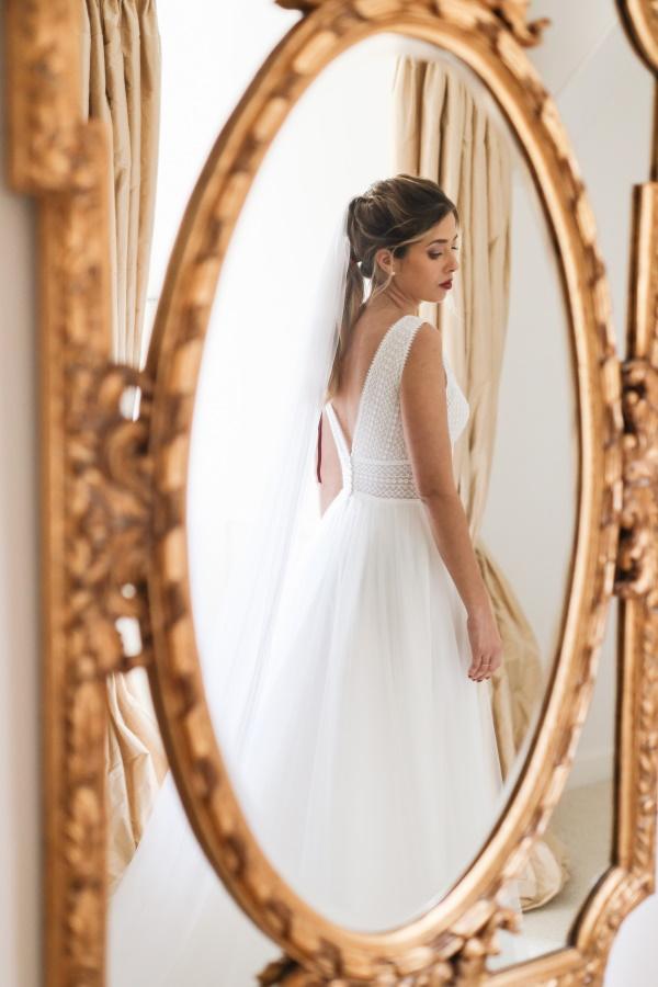La mariée a tourné le dos en réflexion à travers un miroir doré doré