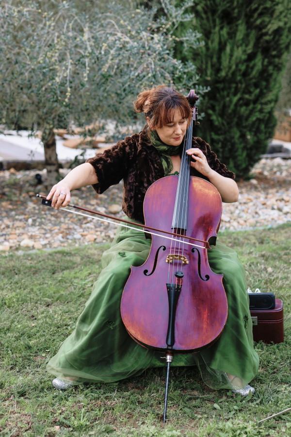 Le violoncelliste joue de la musique d'entrée pour la mariée portant une jupe verte dans le jardin du Château Lacanaud, Dordogne France