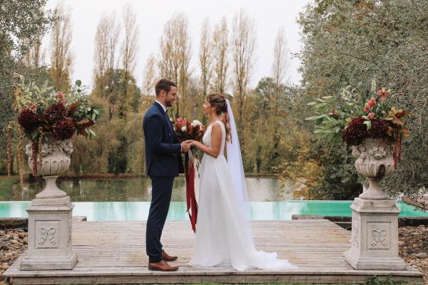 Les mariés se tiennent la main pour leurs vœux devant la piscine extérieure