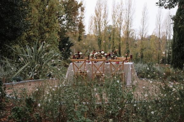 table de mariée dans le jardin entourée de marguerites et habillée de couleurs merlot