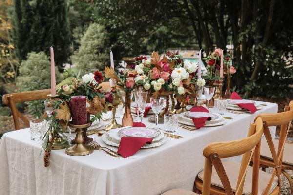 table de mariage en plein air abondante décorée avec des arrangements floraux et de la vaisselle bordeaux et roses