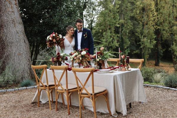 Les mariés se tiennent derrière leur table de mariage en plein air ornée de nappes blanches et de décorations de table bordeaux et roses