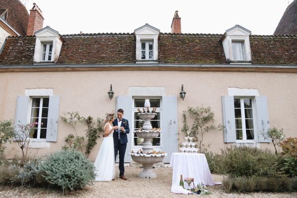 Debout à l'extérieur du château Lacanaud en Dordogne France, les mariés portent un toast le jour de leur mariage à côté de la fontaine de bouteilles de champagne