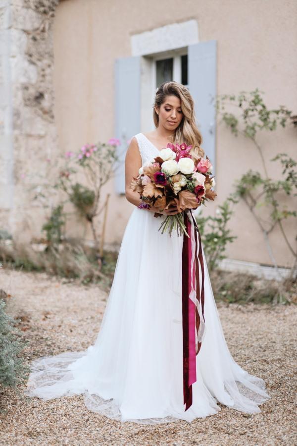 La mariée se trouve à l'extérieur du château Lacanaud en France portant une robe de mariée fluide blanche et détient un grand bouquet bordeaux avec de longs rubans bordeaux