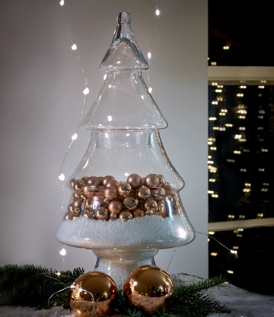 Glass Christmas tree decoration styled with artificial snow and metallic copper baubles