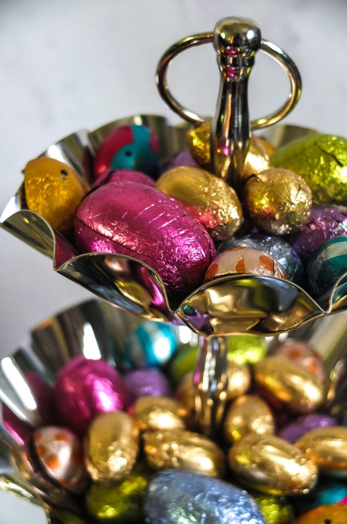 Colourful wrapped mini Easter eggs look delightful displayed in a silver tone two tier decorative cake stand