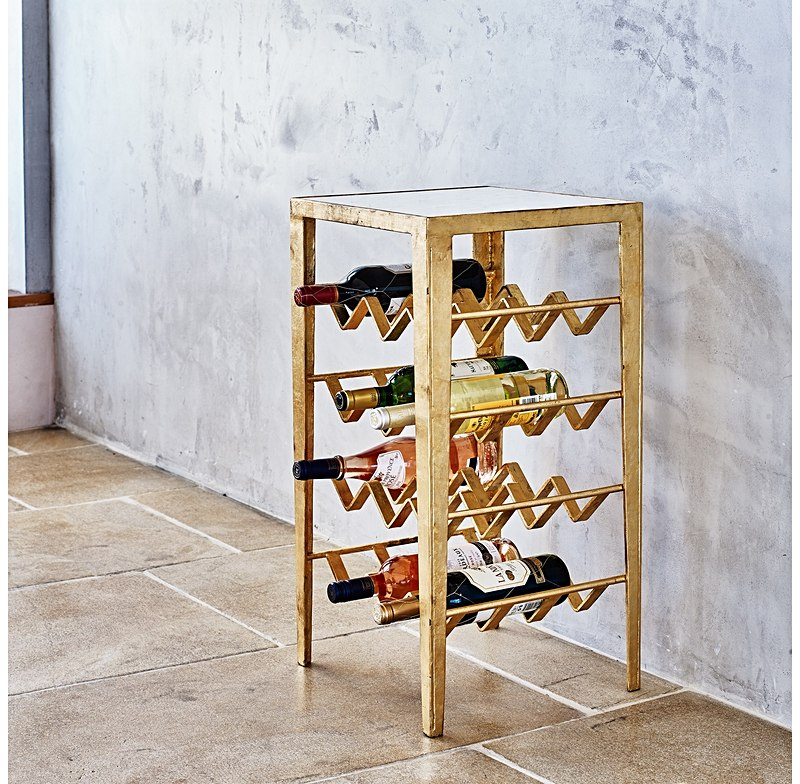 A beautifully designed gold table with marble top that doubles up as a wine rack. The perfect piece for small space.