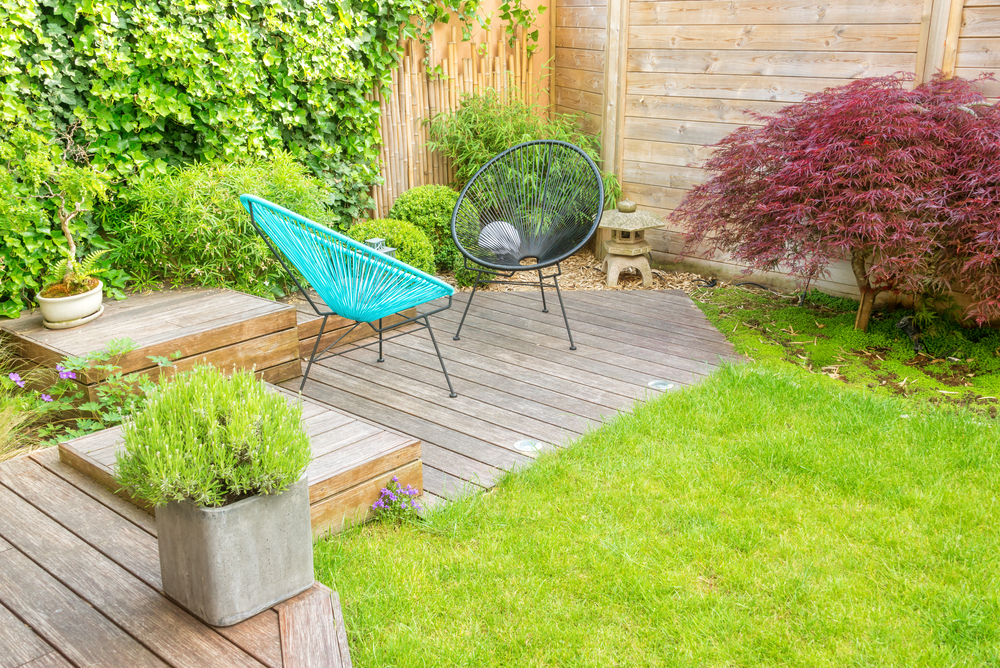 Lovely low maintenance backyard with decking, plants in containers and fences instead of hedges