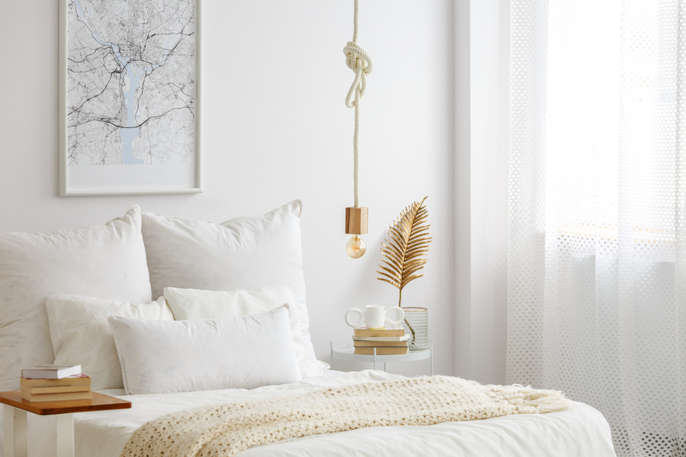 The gold accents and artwork help provide interest in this white bedroom