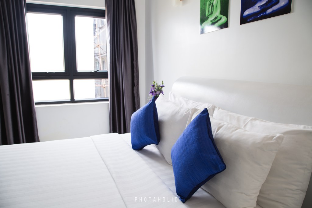 The blue cushions add a pop of colour on this fresh white bedding