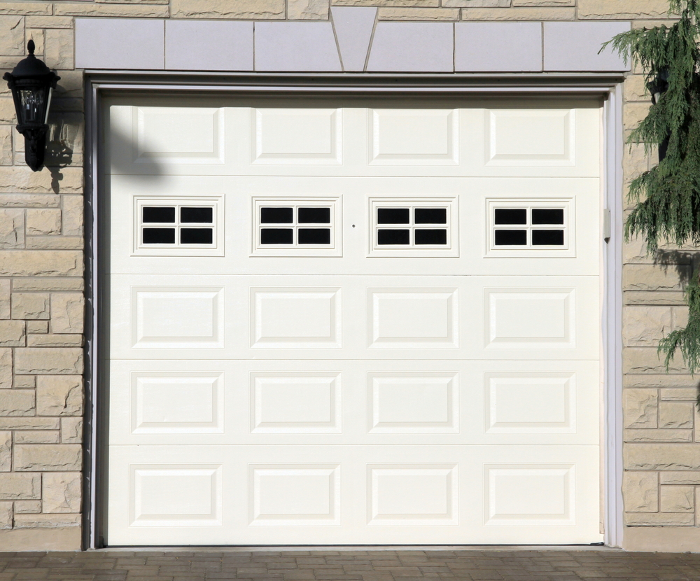 White garage door set with four small windows to add extra light into the room inside