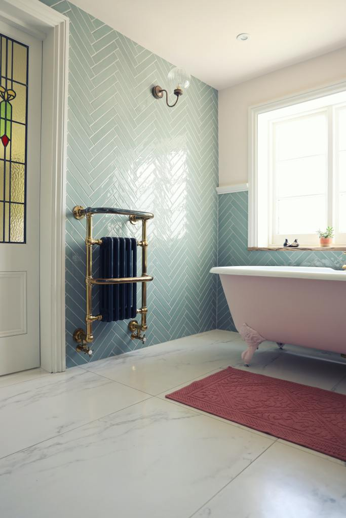 Victorian style bathroom with turquoise tiles and a cast iron style radiator