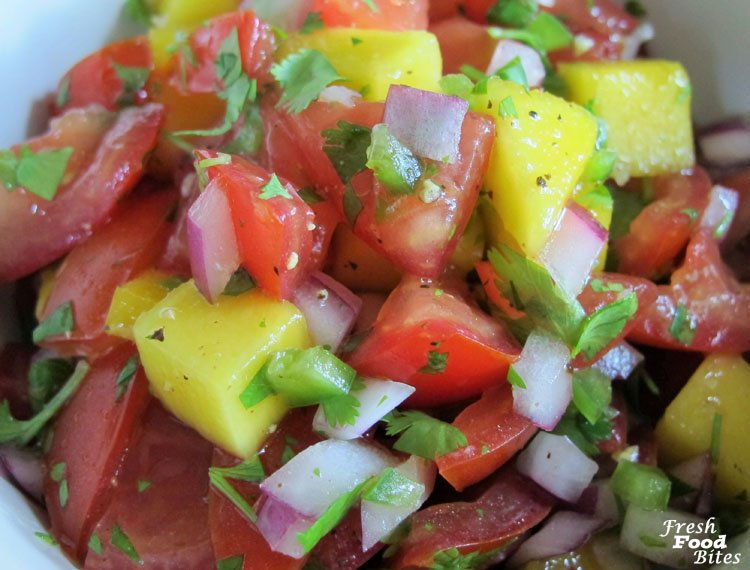 Tomato-Mango Pico de Gallo uses fresh, in season tomatoes, along with fresh mango for a simply sweet match made in heaven. This Pico de Gallo works well as a topping for fish tacos, served with tortilla chips, or spooned over salad greens in place of salad dressing. It's a quick and easy addition to any meal, snack or appetizer buffet.