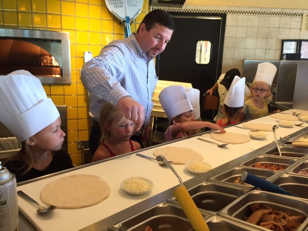 Kelly helps the kids get their pizzas going just right
