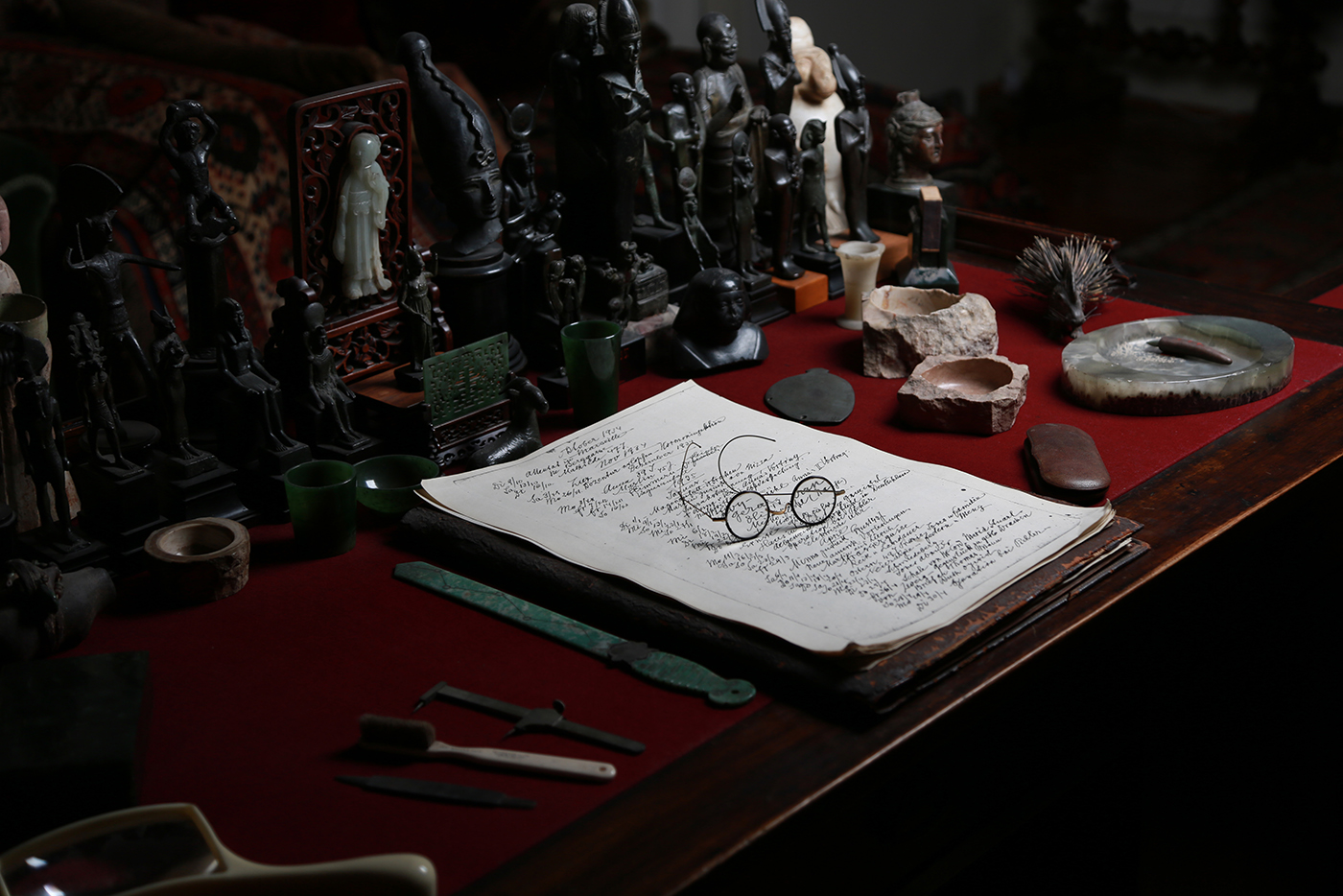 Photograph of Sigmund Freud's desk. On it are some antiquities, a page from his diary and his spectacles.