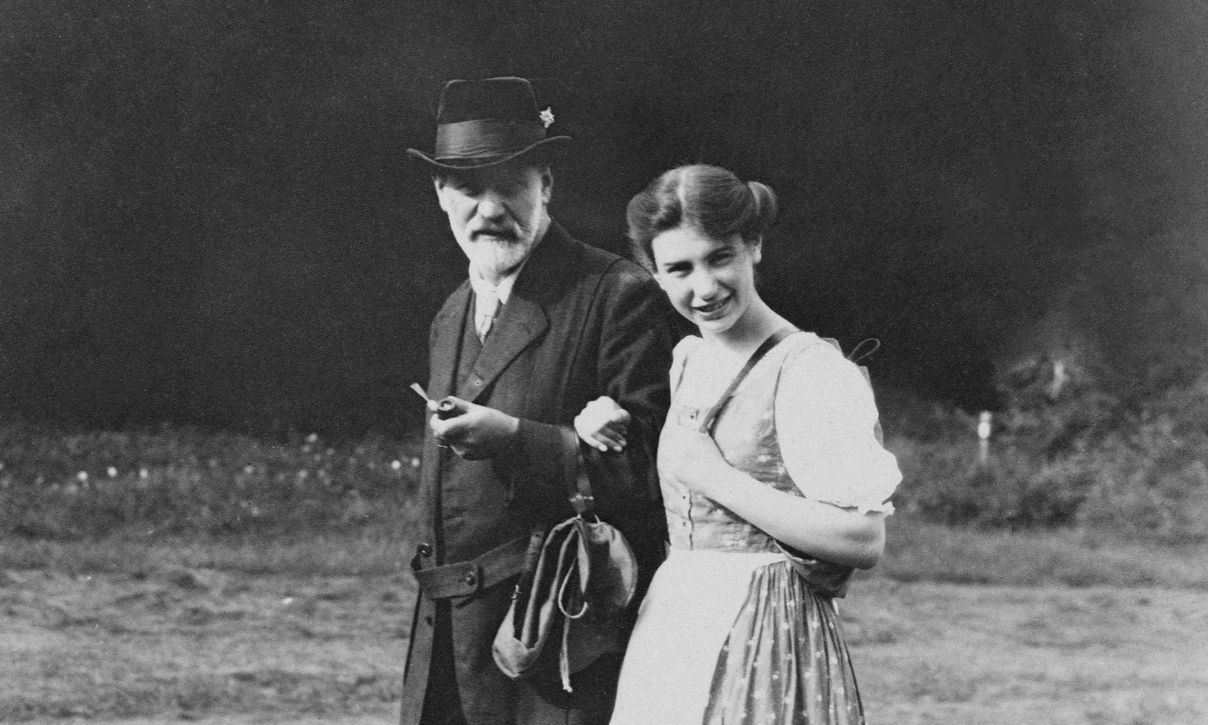 Black and white photograph of Sigmund and Anna Freud walking arm in arm and looking at the camera