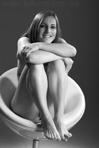 Nackte Frau sitzt provokant sexy auf Hocker