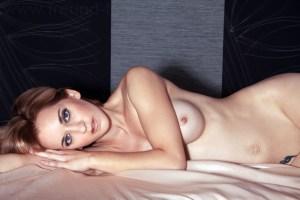 Nackte Frau liegt sinnlich auf dem Bett