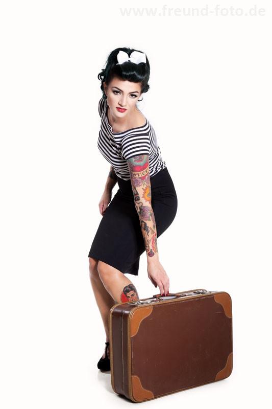 Frau im sexy Pinup Outfit mit alten Reisekoffer