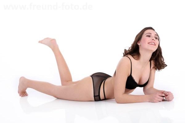 Junge Frau liegt sexy in Unterwäsche auf dem Boden
