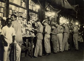 """Corner bookstalls, specializing in lurid novels, sec treatises, are fascinationg spots for British and American soldiers alike. Typical titles, """"The Escapades of Erotic Edna"""", """"Kama Sutra, The Hindu Art of Love""""."""""""