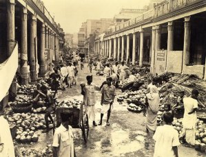 This cocoanut market on Cornwallis stret is a sample of the haphazard way in which many basars are opperated.The popular pauses for refresment is indulged by Indian in central foreground drinking cocoanut milk.