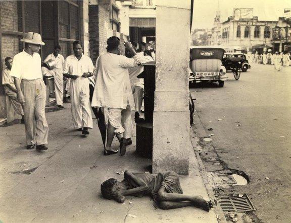 The indifference of the passerby on this downtown Calcutta street to the plight of the dying woman inthe foreground is considered commonplae. During the famine of 1943, cases like this were to be seen in most every block, and though less frequent now, the hardened public reaction seems to have endured.