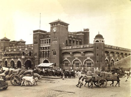 Sacred cattle and coolies push and pull great carts to the loading platform of the Howrah railroad station in background, on of the city's two stations. Howrah is on the west bank of the river, and Sealdah, the other station, is in another section of Calcutta on the east side.