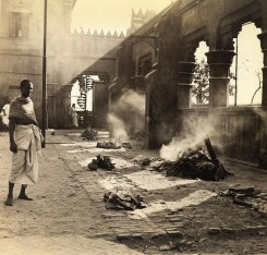 Nimtolla burning ghat where Hindus burn the bodies of their dead and commit the remains to the Hooghlyriver. Several funeral pyres still burn while abandoned baby in foreground awaits burning.