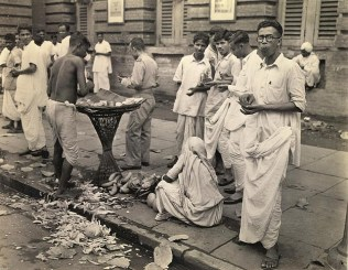 The noon snack is taken by many at a fruit vendor such as this one. Verboten to troops by Millitary order, sanitation isn't even considered and peels litter the streets. Greatest menace of this dealer is the threat of Cholera, carried by flies from open garbage bins to sliced fruit.